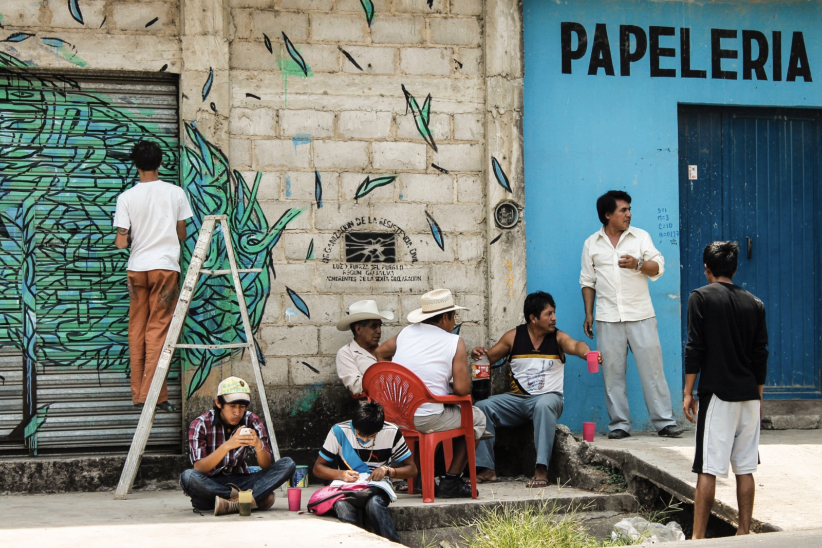 A group of activists sitting in front of one of their houses, while street-artist Crisa paints a mural. The seal of Luz y Fuerza del Pueblo appears on the wall behind them. - Comalapa, Chiapas. April 2014.